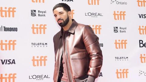 Drake pose devant un mur recouvert de logos du TIFF.
