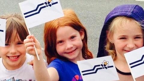 Des fillettes agitent de petits drapeaux franco-colombiens en papier lors d'une journée ensoleillée.