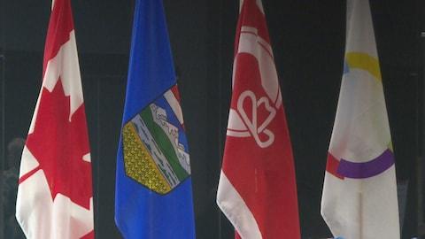 Quatre drapeaux représentants le Canada, l'Alberta et la francophonie.