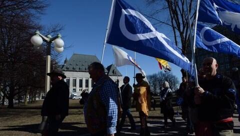 Des gens marchent en tenant le drapeau métis devant la Cour suprême.