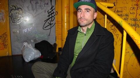 Robert Lidstone est assis dans une cage d'escalier jaune.