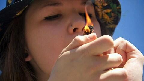 Adolescente fumant un joint.