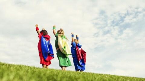 Trois enfants déguisés en super héros sont photographiés de dos.