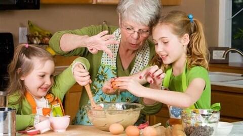 Une grand-mère et ses deux petites-filles qui font de la cuisine.