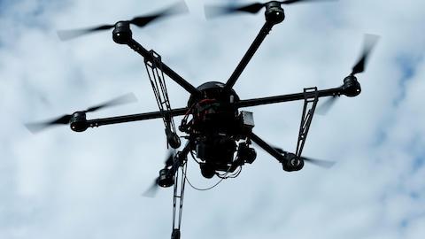 Un appareil ayant six hélices lui permettant de voler est vu dans le ciel.