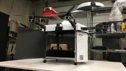 Un drone de forme carrée avec quatre hélices posé sur une table.
