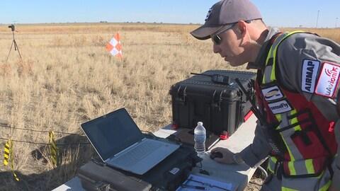 Un scientifique regarde un ordinateur dans un champ lors d'un test aérien d'un drone à la nouvelle zone de tests Point Trotter Autonomous Systems Testing Area.
