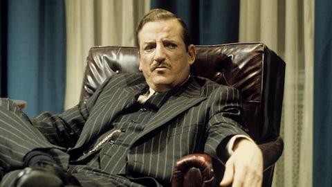 Le premier ministre Maurice Duplessis (Jean Lapointe) assis, jambes croisées, dans un fauteuil en cuir brun.