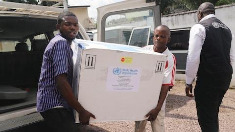 Des personnes ont dans les mains une boîte avec du matériel médical provenant de l'OMS.