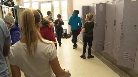 Des élèves se tiennent près de leur case dans une école.