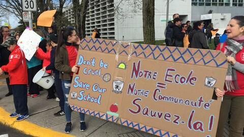 Des pancartes bilingues présentées par des manifestants sur le trottoir.