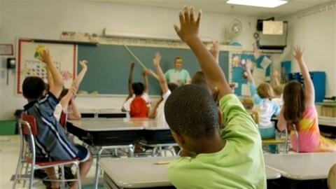 Des élèves lèvent la main pour répondre à une question de leur enseignant.