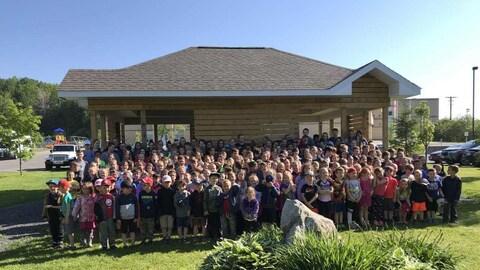 Des dizaines d'élèves forment plusieurs rangs devant la classe extérieure.