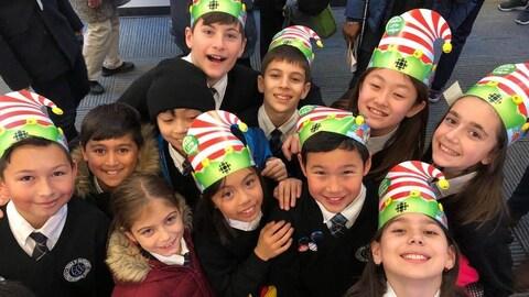 Des écoliers souriants et  portant un uniforme dans la salle de nouvelles de Radio-Canada lèvent ensemble la tête vers l'appareil photo.