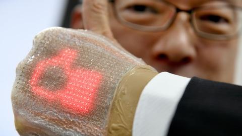 Un homme portant un écran lumineux très mince autour de sa main lève le pouce.