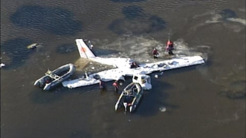 La carcasse d'un avion gît dans l'eau. Des secouristes avec leurs zodiacs se trouvent autour.