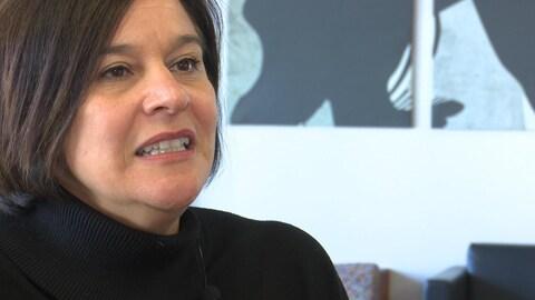 Une femme autochtone accorde une entrevue à un journaliste hors-champ.