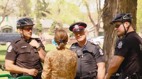 Une femme, vue de dos, parle à trois policiers sur le bord d'un parc de quartier.