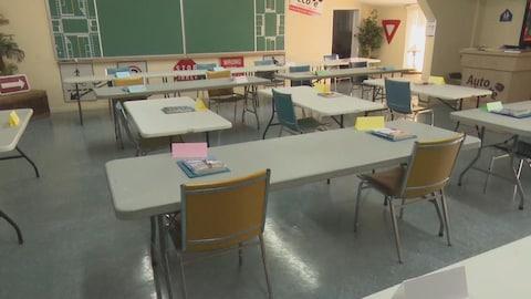 Des tables et des chaises disposées à une bonne distance les unes des autres dans une salle de classe.