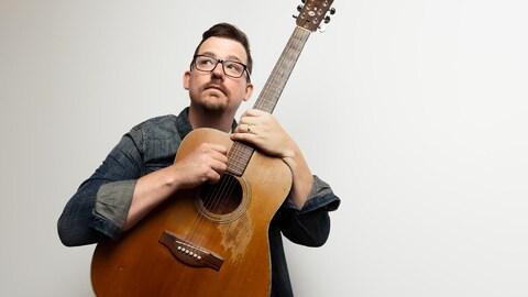 Photo de l'artiste en chemise noire avec une guitare sèche entre les mains.