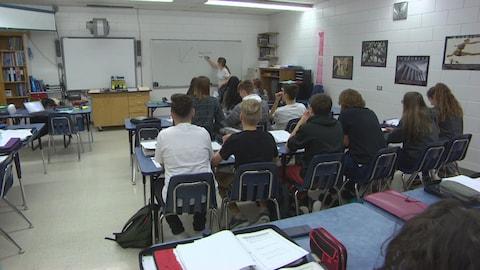 Des élèves assis à leurs bureaux écoutent leur enseignante, qui trace un graphique mathématique au tableau.