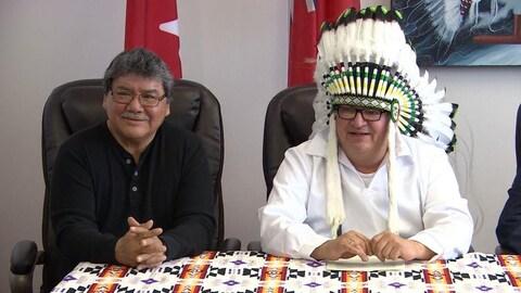 Deux chefs autochtones posent devant la caméra. L'un est tête nue avec une chemise noire et des lunettes. L'autre porte une chemise blanche, une coiffe autochtone et des lunettes.