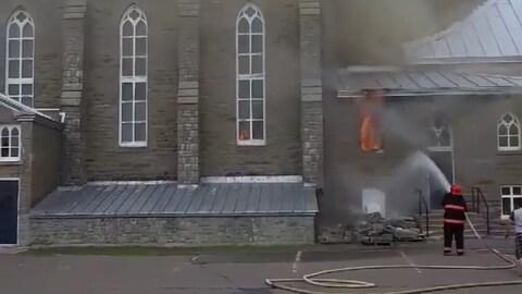 Des flammes s'échappent d'un vitrail endommagé. Un pompier arrose le brasier.
