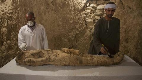 Des Égyptiens restaurent une momie dans une tombe nouvellement découverte à Louxor.