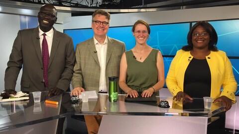 Quatre personnes regardent la phoptographe en souriant; elle sont debout derrière une table dans un studio de télévision.