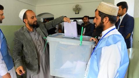 Un électeur afghan dépose son bulletin de vote dans l'urne, dans la province de Herat, à l'occasion des élections législatives le 20 octobre 2018.