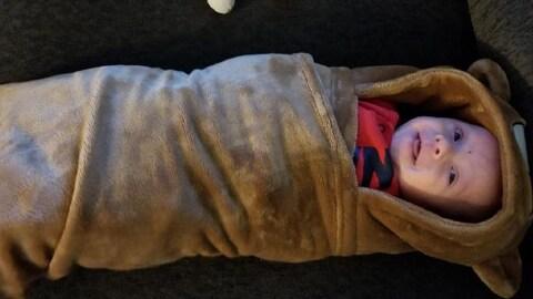 Elijah est enveloppé dans une douillette brune avec des oreilles d'ourson. Il sourit à la caméra.