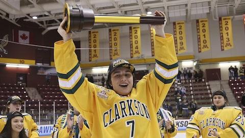 Auteure du but gagnant en prolongation, Elizabeth Giguère soulève le trophée remis à l'équipe championne du hockey universitaire américain (NCAA)