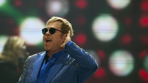 Elton John, sur scène, porte un costume bleu et des lunettes de soleil et écoute la foule chanter.
