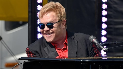 Elton John, assis derrière un piano, sourit en regardant le public.