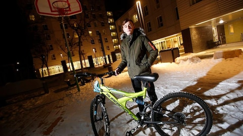 Emad Tamo tient le guidon d'un vélo debout dans la neige devant un immeuble.