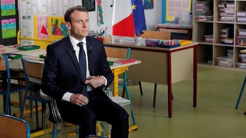 Emmanuel Macron, assis sur une chaise dans une salle de classe d'une école primaire.