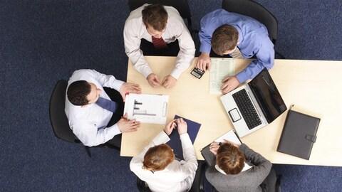 Travailleurs autour d'une table en réunion.
