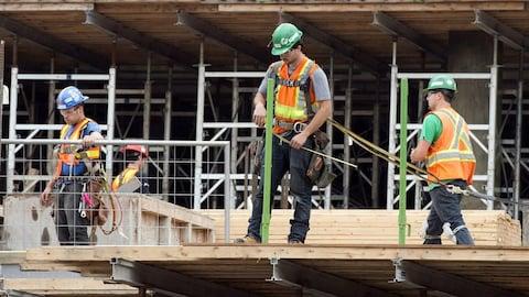Des hommes portant un casque de protection et des dossards sont vus sur un chantier de construction.