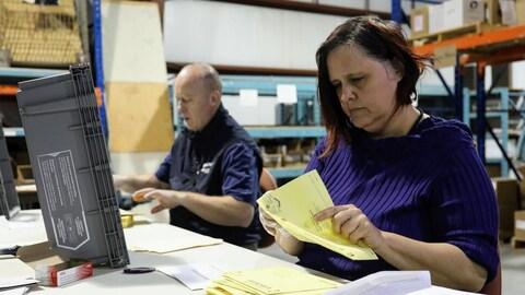 Des employés sont assis et ouvrent des enveloppes.