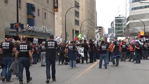 Des manifestants vêtus de t-shirts sur lesquels est écrit Négo 2018.