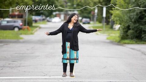 Une femme souriante et qui a les bras grand ouverts dans le milieu d'une rue.