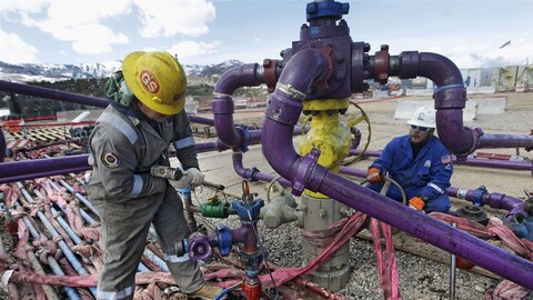 Des employés d'Encana travaillent sur un puits pétrolier.