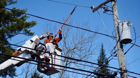 Un travailleur d'Énergie NB, dans une nacelle, tente de réparer une ligne électrique.