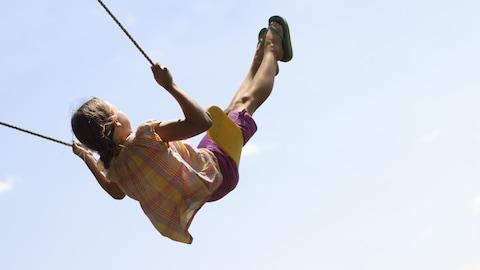 Une petite fille s'élance sur une balançoire.