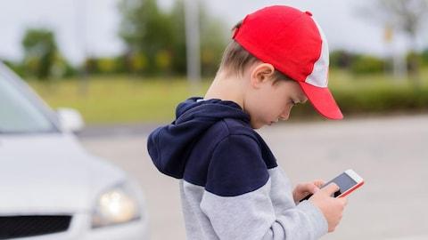 Un petit garçon joue sur son cellulaire.