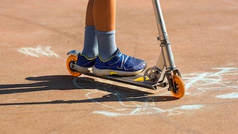 Gros plan sur les chaussures d'un garçon debout sur une trottinette.