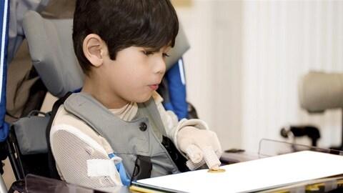 Un enfant handicapé utilise un clavier tactile