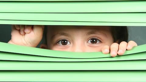 Un enfant regarde entre les lattes d'un store.