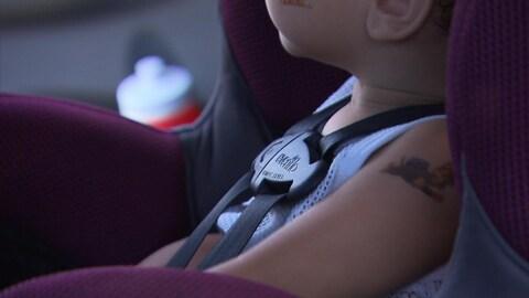 Une enfant est assise dans un siège d'auto et la ceinture de sécurité est bouclée.