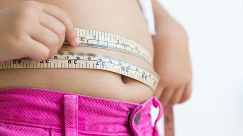 Une jeune fille mesure son tour de taille avec un ruban à mesurer.